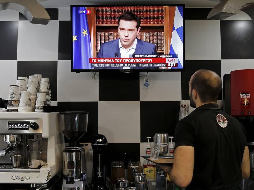 """Garçom assiste ao pronunciamento do primeiro-ministro grego Alexis Tsipras, em Atenas, Grécia. Tsipras pediu para que os gregos votem """"não"""" no referendo de domingo"""