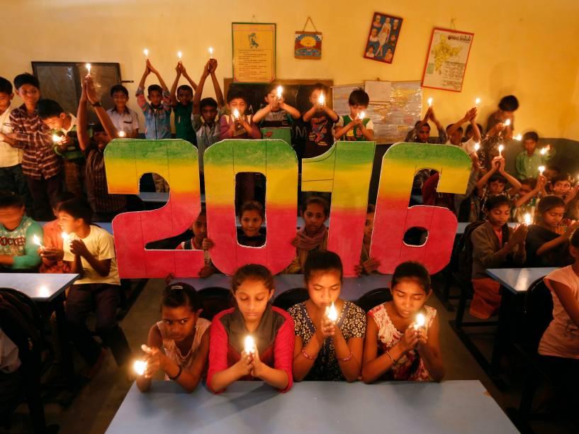 Em Ahmedabad, na Índia, crianças fazem orações pedindo a paz mundial no próximo ano de 2016