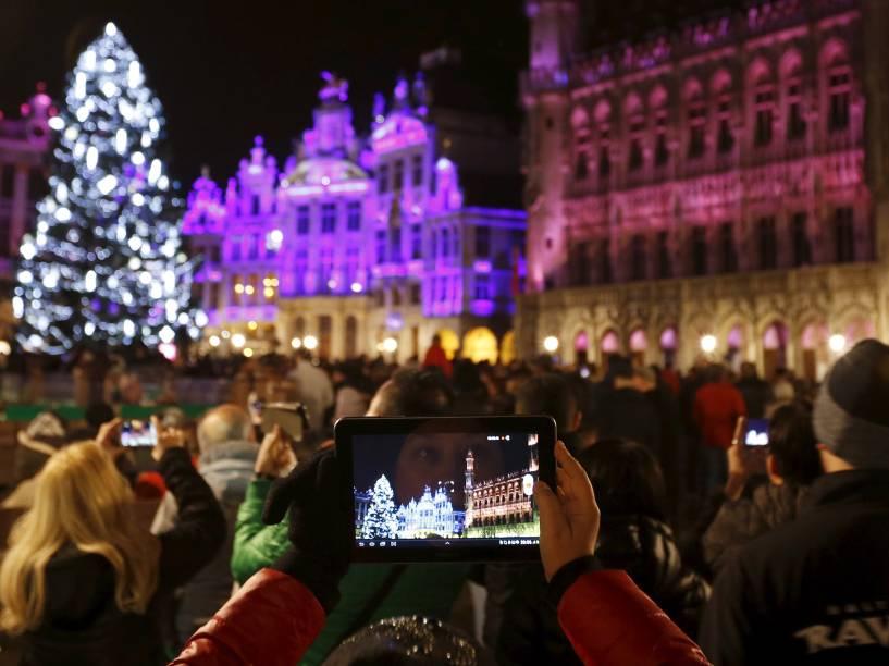 Turista tira fotos do show de luzes na véspera de ano novo em frente ao Palácio Real de Bruxelas