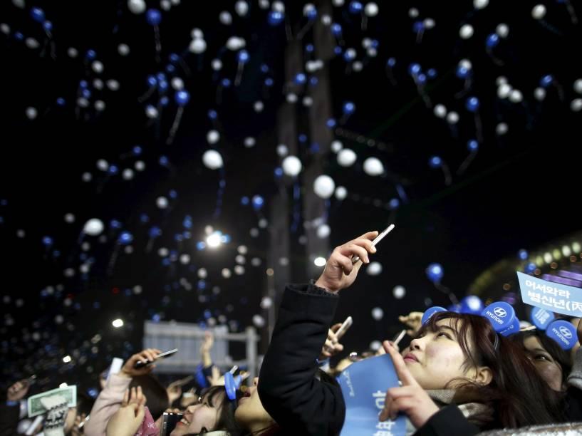 Mulher fotografa os balões soltos durante a comemoração do ano novo em Seul, Coréia do Sul
