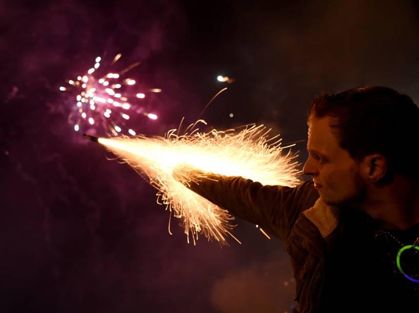 Homem dispara um sinalizador durante celebrações de Ano Novo na cidade alemã de Colônia