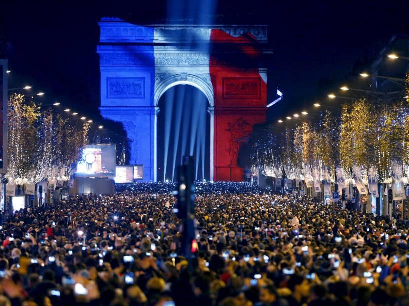 Milhares de pessoas se reúnem perto do Arco do Triunfo, iluminado com as cores da bandeira francesa na Avenida Champs Elysees , em Paris, durante as celebrações de Ano Novo