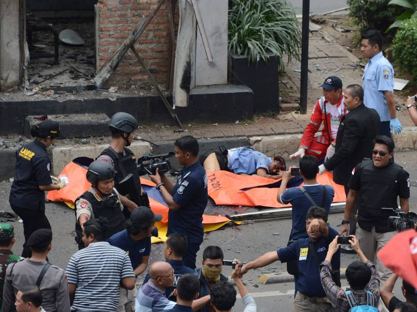 Polícia verifica vítimas de um ataque diante de um posto de polícia, em Jacarta, na capital da Indonésia