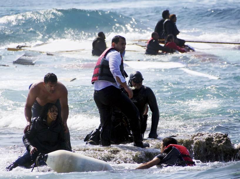 Imigrantes que tentaram chegar à Grécia, são resgatados por membros da Guarda Costeira grega e moradores perto da costa da ilha do sudeste de Rodes