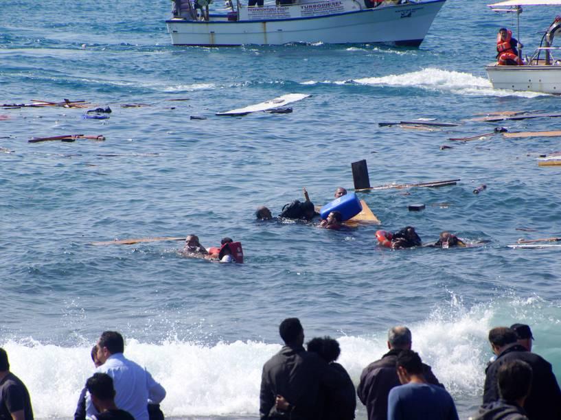 Moradores locais e equipes de resgate tentam ajudar os imigrantes após barco naufragar na ilha de Rodes, sudeste da Grécia