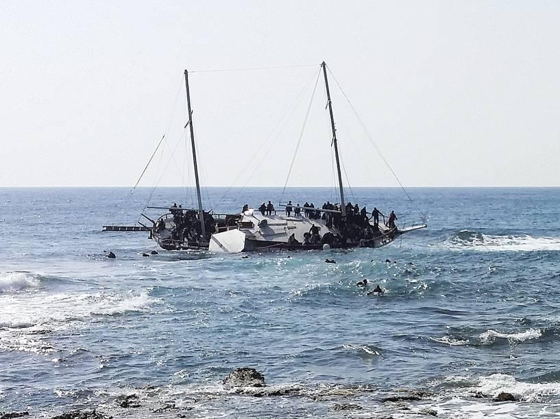 Imigrantes que tentavam chegar a Grécia, são vistos na água tentanto alcançar a costa da ilha de Rodes