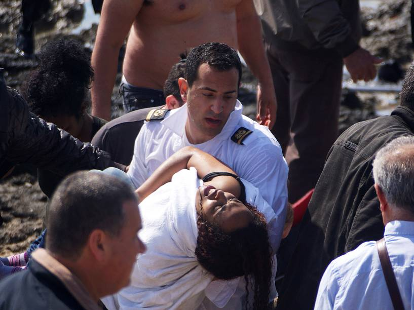 Equipe de resgate ajudam os imigrantes depois de barco naufragar