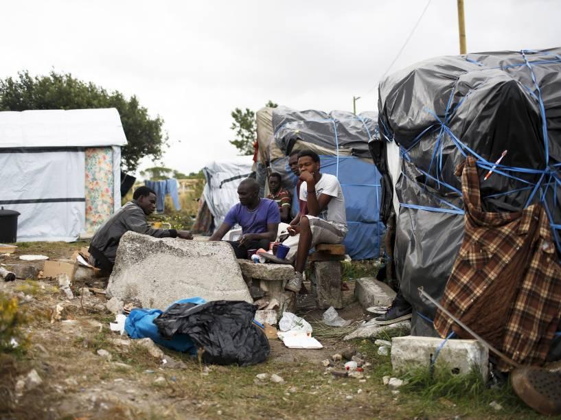 Imigrantes sudaneses em acampamento improvisado perto de Calais, norte de França