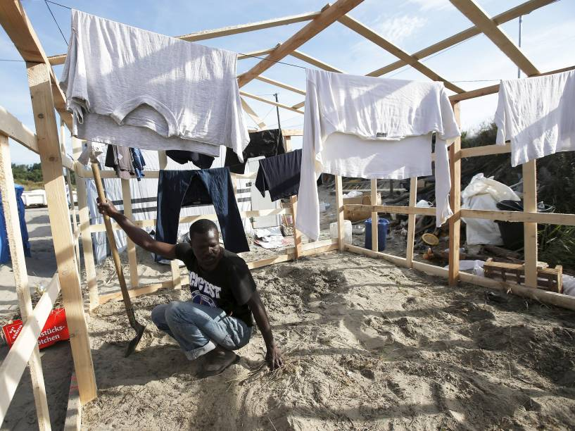 Imigrante trabalha em acampamento improvisado em Calais, norte da França