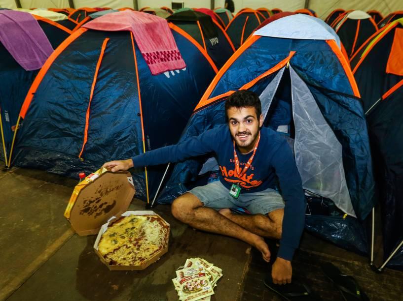 """As pizzas se tornaram a principal alimentação do campuseiro. Na barraca, Felipe Augusto da Silva, 19 anos, esperava um amigo para o jantar. """"Vi pessoas que comeram pizza todas as noites"""", diz o estudante do Rio Grande do Sul"""