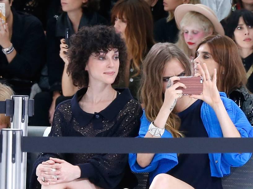 A cantora St. Vincent e a modelo Cara Delevingne são vistas usando o mesmo anel no dedo anelar durante a Paris Fashion Week