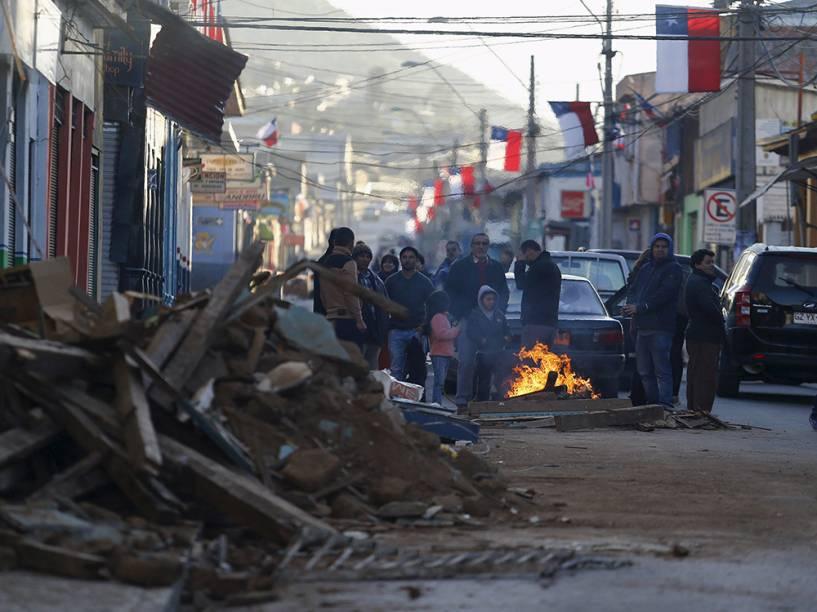 Pessoas recolhem destroços depois do terremoto que atingiu a zona central do Chile
