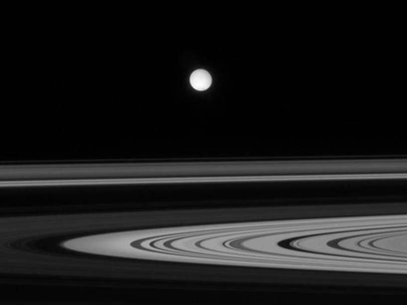 <p>Os anéis de Saturno e sua lua Enceladus em imagem registrada pela sonda Cassini da Nasa</p>