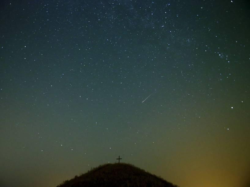<p>Um meteoro cruza o céu sobre a colina Leeberg durante a chuva de meteoros Perseidas perto Grossmugl, na Aústria - 13/08/2015</p>
