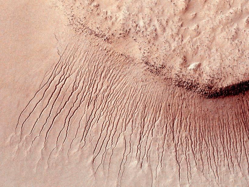 <p>Superfície marciana fotografada pela missão Mars Reconnaissance Orbiter (MRO) em 2011, mostra uma série de canais de um a dez metros de largura em uma escarpa na bacia de Hellas</p>