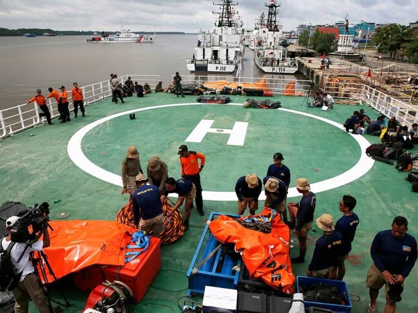Mergulhadores da Marinha da Indonésia prepararam equipamentos na plataforma de um navio das forças nacionais antes da operação de busca aos passageiros do AirAsia QZ8501, no porto Kumai, no mar de Java