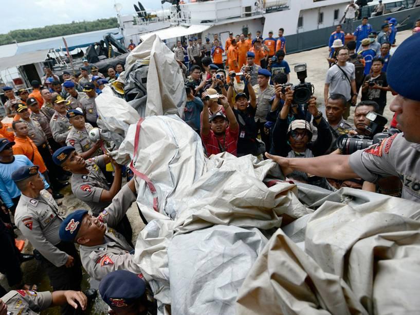 Policiais transportam os restos de um barco que se acredita ser um escorregador de emergência do AirAsia QZ8501, no porto de Kumai, no mar de Java