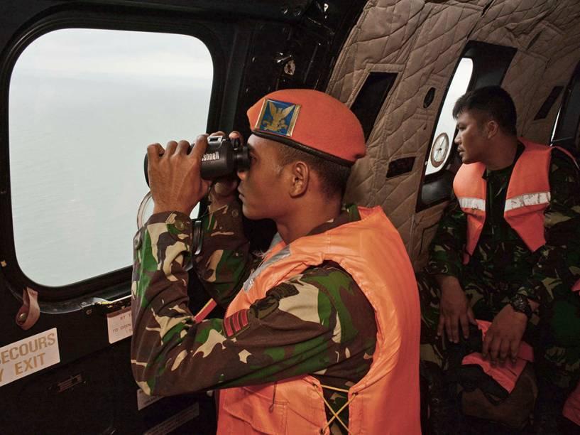 Soldado da Força Aérea da Indonésia usa um binóculo durante as operações de busca das vítimas do voo AirAsia QZ 8501 sobre o Mar de Java