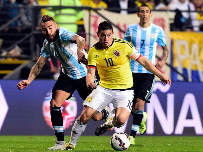 O meia colombiano James Rodríguez passa pela marcação do argentino Nicolás Otamendi