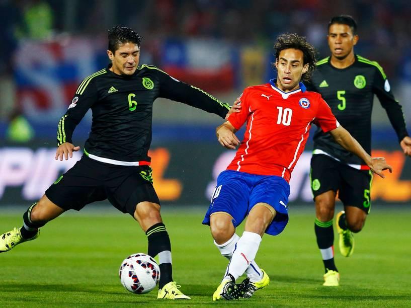 O mexicano Javier Güemez disputa jogada com o chileno Jorge Valdivia em partida disputada no Estádio Nacional em Santiago