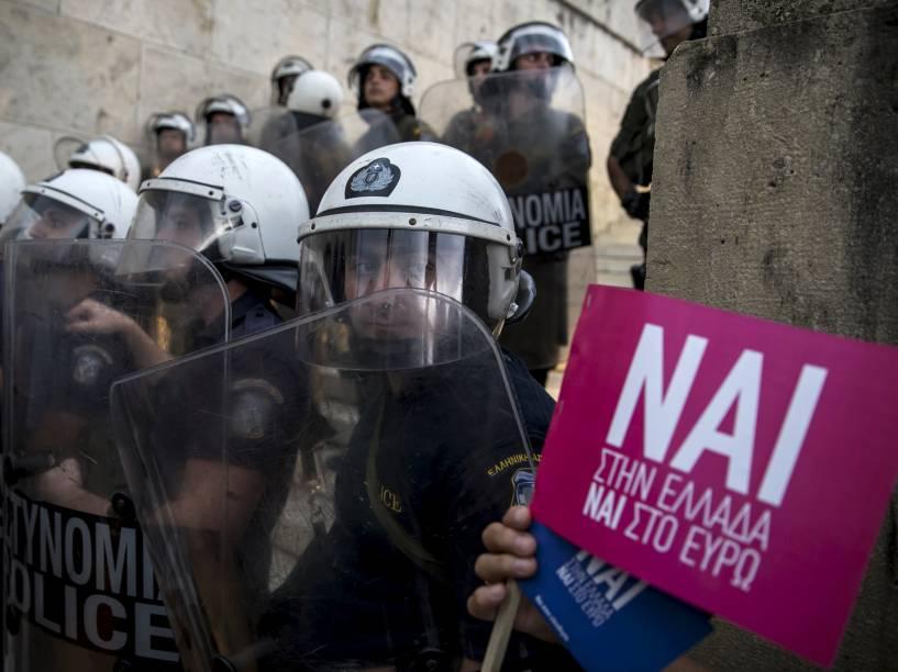 Tropas da polícia de choque se posicionam em frente ao parlamento grego, em Atenas, durante protesto a favor da permanência do país na zona do euro