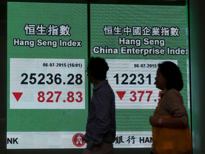 Pessoas passam em frente a um painel com o fechamento da bolsa em Hong Kong, China. O mercado fechou em queda devido ao receio dos investidores de que a crise da Grécia venha a piorar