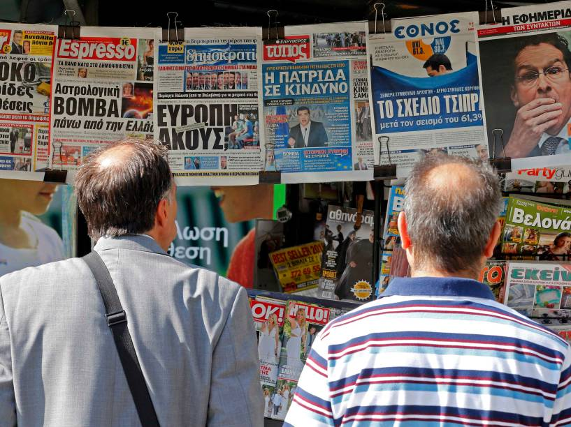Pessoas olham para jornais com os resultados do referendo de domingo (6) em bancas no centro de Atenas, Grécia. Cerca de 61% dos gregos negaram as condições de resgate dos credotes em votação no domingo (5), deixando o futuro do país na zona do euro cada vez mais incerto
