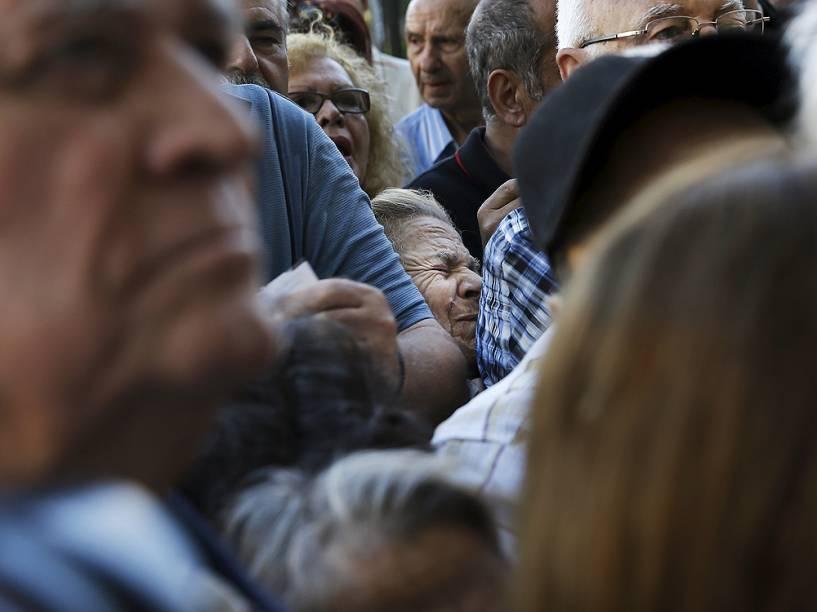 Aposentados gregos aguardam na fila em agência bancária em Atenas nesta quarta-feira (1º) após governo permitir que eles façam saques acima de limite imposto