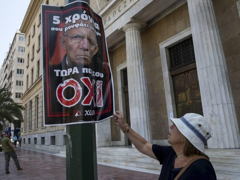 Mulher observa um pôster no centro da Grécia que mostra uma imagem do ministro das Finanças alemão, Wolfgang Schaeuble, com o slogan: Há cinco anos ele vem sugando seu sangue