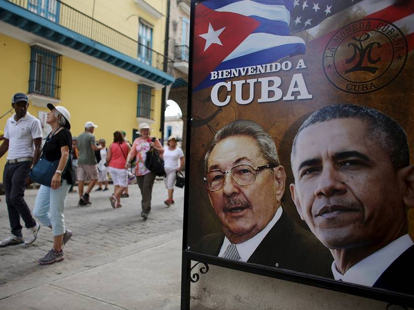 """Turistas passam por imagem do Presidente americano Barack Obama e o Presidente cubano Raul Castro, com os dizerem """"Bem-vindo a Cuba"""""""