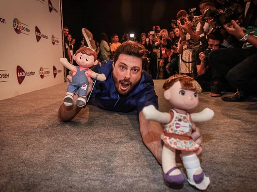 Danilo Gentili faz graça e se joga no chão com os bonecos Tonzinho e Nina durante o Teleton 2015 nos estúdios do SBT em São Paulo