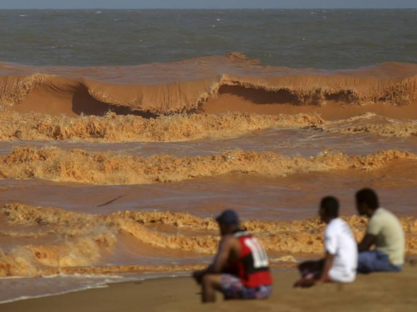 Homens observam o Rio Doce repleto de lama com rejeitos vindos da barragem de Mariana (MG), enquanto o rio se encontra com o mar em Espírito Santo