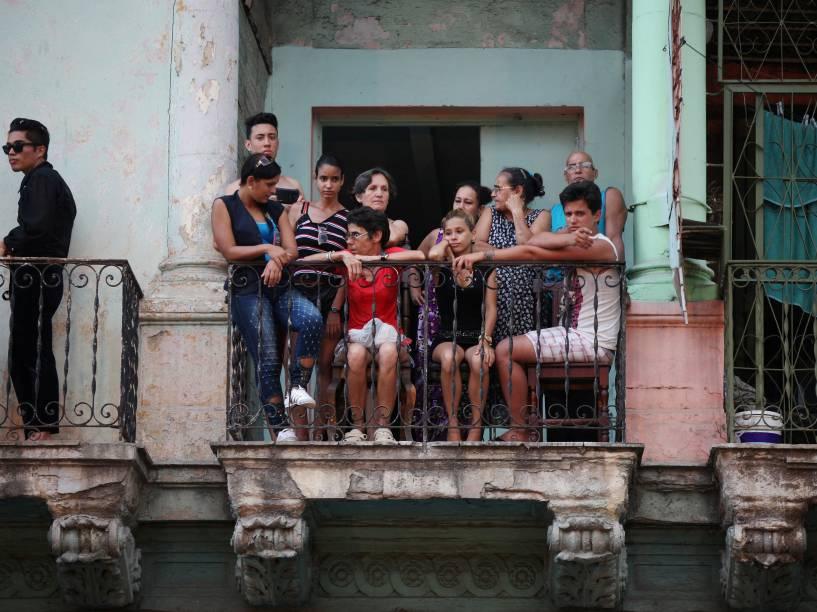 Cidadãos cubanos se acomodam em uma sacada para acompanhar o desfile da Chanel em Havana - 03/05/2016