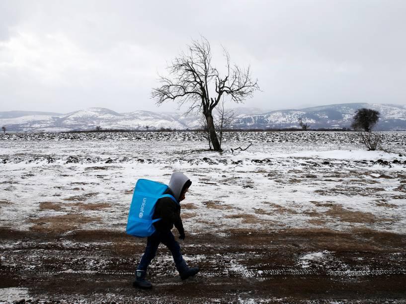 Uma criança refugiada caminha por um campo coberto de neve depois de cruzar a fronteira da Macedônia, em Miratovac, na Sérvia