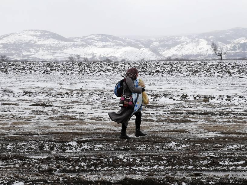 Uma refugiada caminha por um campo coberto de neve depois de cruzar a fronteira da Macedônia, em Miratovac, na Sérvia