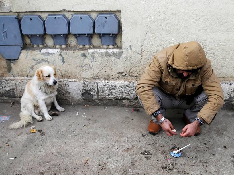 Um cão senta-se ao lado de um imigrante que espera por um trem partir para a Croácia na estação de Presevo, Sérvia