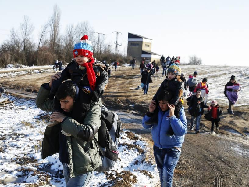 Imigrantes caminham por um campo coberto de neve depois de cruzar a fronteira da Macedônia, em Miratovac, na Sérvia