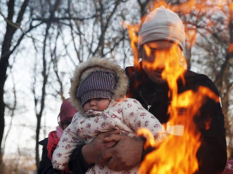 Refugiados se aquecem em fogueira na fronteira da Macedônia, em Miratovac, na Sérvia<br><br>