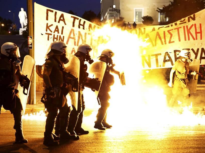 Polícia de choque fica entre as chamas das bombas de gasolina jogadas por um grupo de manifestantes em frente ao parlamento em Atenas, na Grécia - 15/07/2015