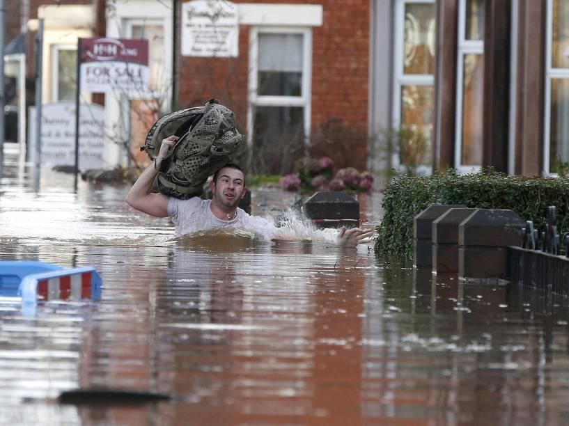 Morador de Carlisle, na Grã-Bretanha, tenta se proteger de tempestade após fortes chuvas na região
