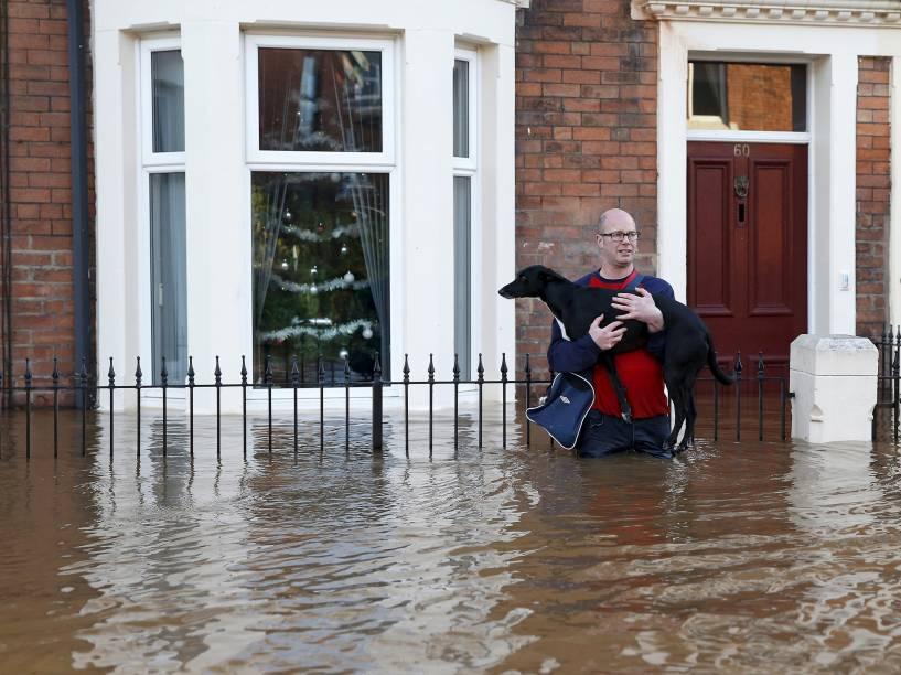 Morador local segura seu cão durante tentativa de atravessar uma rua inundada em Carlisle, Grã-Bretanha