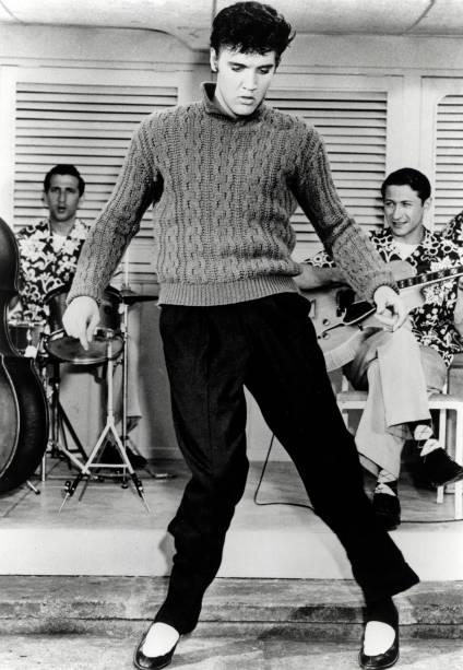 Elvis Presley canta e dança com sua banda em um filme no ano de 1956