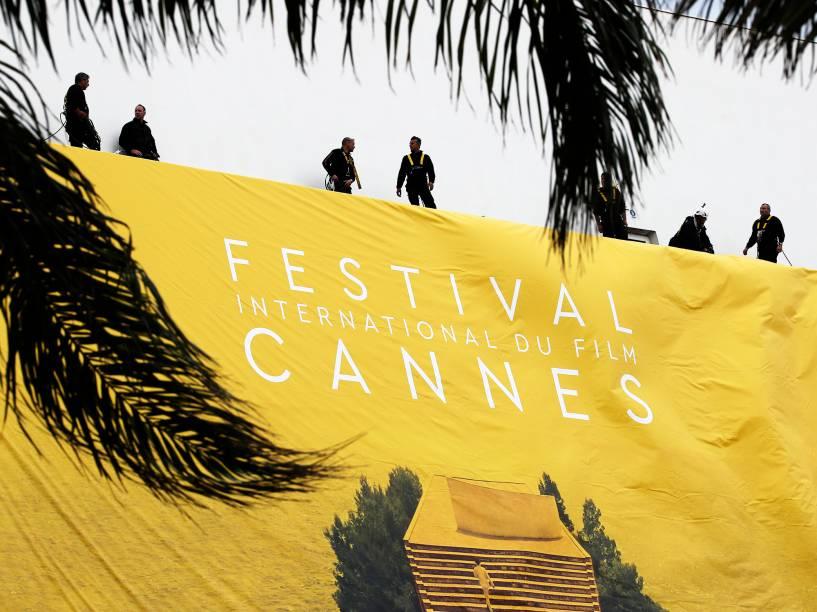 Trabalhadores estendem banner do Festival Internacional de Cannes, no Palais des Festivals, no Sul da França - 10/05/2016