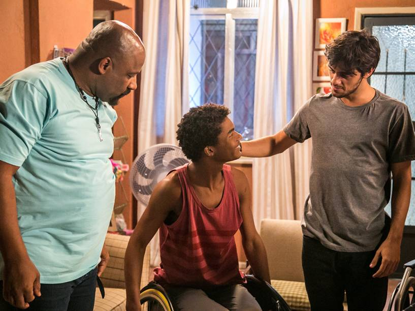 Wesley (Juan Paiva) emocionado, admirando a cadeira. Rô (Malu Galli) e Jenny (Lellezinha) com ele, em capítulo da novela Totalmente Demais
