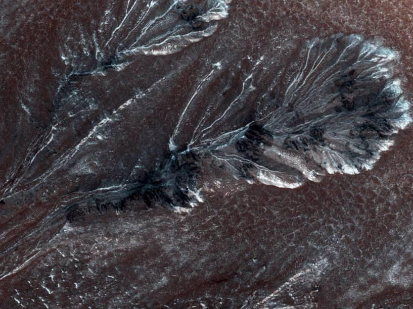 <p>Esta imagem, capturada em 30 de julho de 2015 pela Missão Mars Reconnaissance Orbiter (MRO), retrata uma geada sazonal que se forma em médias e altas latitudes de Marte. Segundo cientistas, esse fenômeno é bem parecido com a neve na Terra e pode causar as voçorocas na superfície marciana.</p>