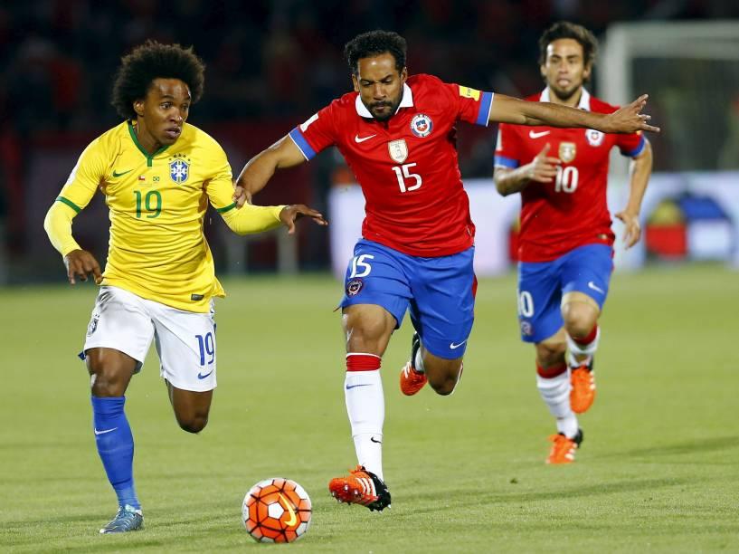 O meia William do Brasil controla a bola sob a marcação do volante Jean Beausejour do Chile