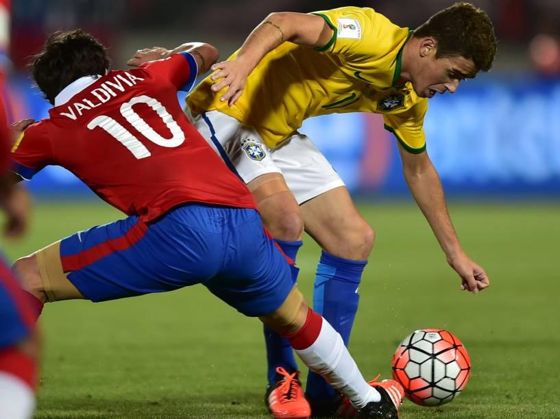 O meia brasileiro Oscar divide jogada com o chileno Jorge Valdivia