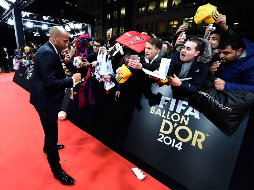 O francês Thierry Henry autografa pertences de fãs na entrada da Bola de Ouro, evento da FIFA em Zurique