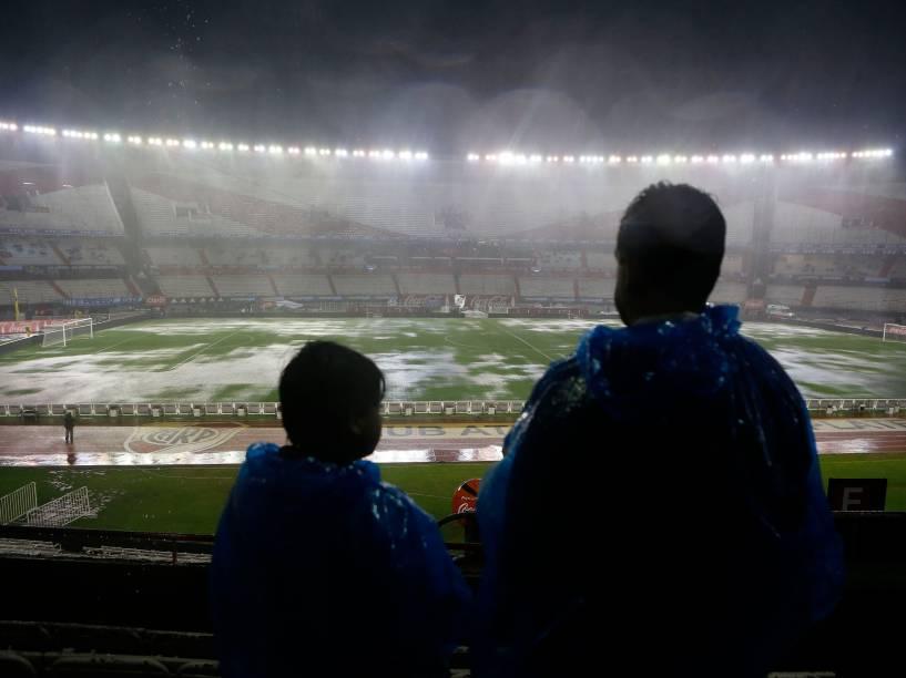 Torcedores observam o gramado do estádio Monumental de Nuñez atingido pela forte chuva antes da partida entre Brasil e Argentina pelas eliminatórias da Copa 2018, em Buenos Aires - 12/11/2015