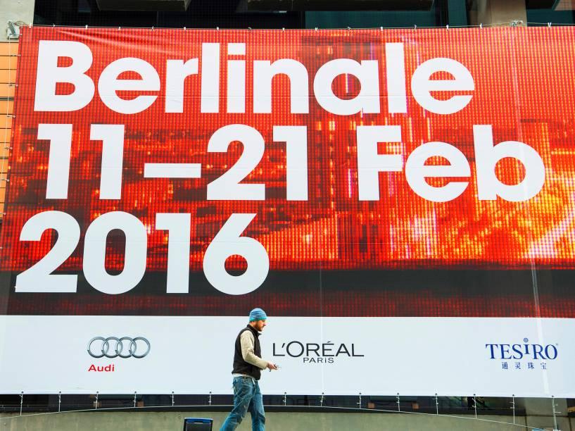 Trabalhador caminha na frente de um outdoor, em frente a um cinema, anunciando o Festival de Cinema de Berlim, na Alemanha